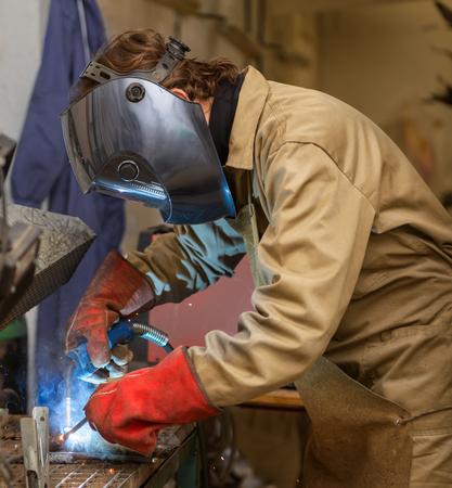 sculptor: Sculptor welding a metal piece Stock Photo