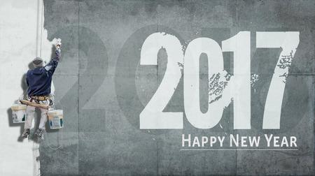 Hormigón: La construcción de pintor que cuelga de arnés de pintura de una pared con las palabras Feliz Año Nuevo 2017