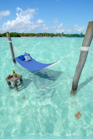 Hammock hanging on top of turquoise water on a tropical beach
