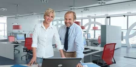 Smiling Man and woman working in a corporate office