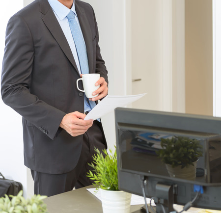 business man with coffee mug reading a document