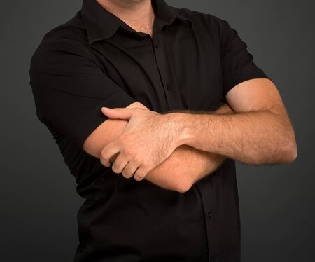 Anonymous man in a black shirt with crossed arms Imagens