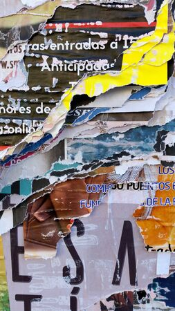 Ripped posters on a street wall showing many layers