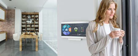 Woman having coffee by a Home automation control station in a modern home Banco de Imagens
