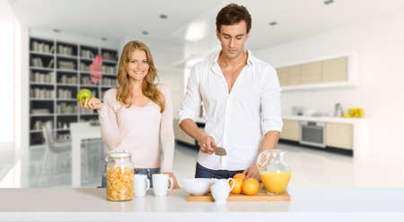 Young couple prepairing a healthy breakfast in a modern luxurious interior 免版税图像
