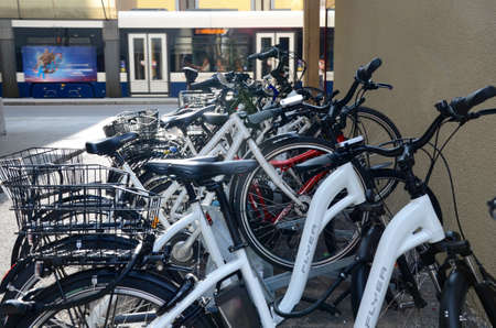 A tram passes next to bicycles parked along a street in Geneva Editorial