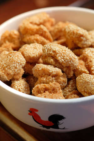 A close up of a bowl of Chinese sesame cookies. It is a traditional Chinese New Year festival snack in Guangdong province. Its also has a nickname of laughing mouth cookie. Banco de Imagens