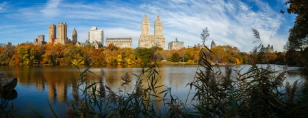 enhances: Urban view of Manhattan, New York, from the Lake in Central Park in autumn  The morning light enhances the colorful trees by the lake and plays on the water surface reflecting Upper West Side buildings  Panoramic viewpoint
