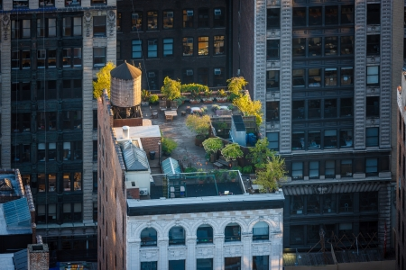 rooftops: Aerial view of a lovely late afternoon light flooding a midtown roof garden in Chelsea, Manhattan, NYC  Rooftop brightened up by sunlit plants, garden furniture and water tower, creating the right atmosphere for a nice, quiet rest among the rooftop planti Stock Photo