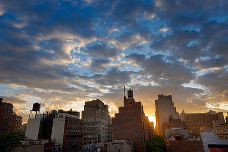 chelsea: Blue hour over Manhattan, New York, and its skyline dotted with water tanks. The sunset enhances the clouds in the evening light and gives off a warm orange glow on Chelsea buildings.