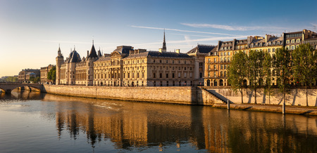 right bank: View of the River Seine right bank on a quiet sunny morning. Glowing morning light showcasing the Conciergerie, Quai de l Horloge and residential buildings on the Ile de la Cit?, in the heart of the City of Lights (1st arrondissement). Panoramic