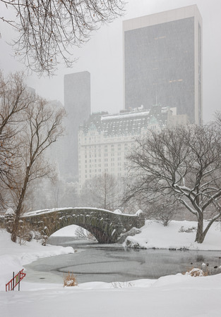Snow falling on the Ponds frozen surface and Gapstow Bridge, and turning Central Park and Manhattan quiet. Peaceful winter scene in New York during a snowstorm. photo