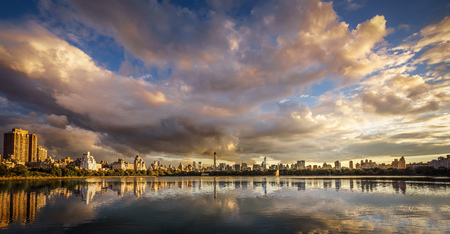 enhances: Sunset light over Jacqueline Kennedy Onassis Reservoir, Central Park, NYC. Evening sky enhances the contrasts between the deep blue sky and the big clouds reflecting on the surface of JKO Reservoir. Cityscape from the Reservoir, with a view of Midtown,