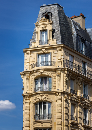 decorative balconies: Haussmannian building in the heart of Paris (12th arrondissement). Haussmannian architectural style showcasing its decorative stonework, wrought iron balconies, a slate mansard roof and its dormer windows. This building was built in 1900. Stock Photo