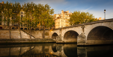 color silence: Morning sunlight spreading over the buildings on Ile Saint Louis and the aspen trees lining the Seine river bank by Pont Marie. Peaceful summer morning in Paris 4th arrondissement. Stock Photo