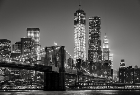 Black & White cityscape by night. View of Brooklyn Bridge, Downtown Manhattan (Lower Manhattan) and the Financial District. NYC skyline with Manhattan skyscrapers lit up at night. Stock Photo