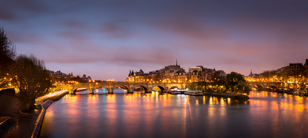 morning blue hour: Sunrise in the heart of Paris, France with Ile de la Cite and Pont Neuf. A calm Seine River reflects the pink and purple sky and the orange glow of the city lights.