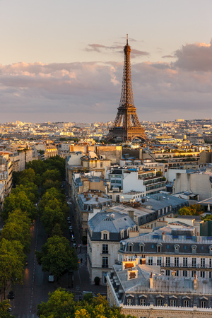 right bank: Avenue Iena looking toward the Eiffel Tower illuminated by summer sunset light. Elevated view of rooftops in the heart of Paris, Right Bank of capital city in the 16th arrondissement, Ile de France.