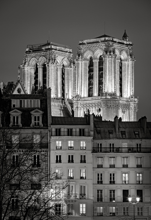 ile de la cite: Two towers of Notre Dame de Paris Cathedral illuminated at night. The French Gothic cathedral architecture contrasts with facades of 19th century private houses on Ile de La Cite, Paris, France