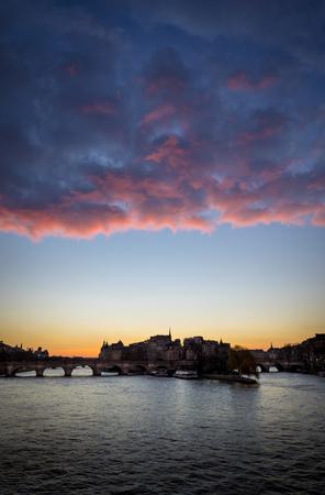 ile de la cite: West end of Ile de la Cite at sunrise with glowing pink clouds. The Pont Neuf crosses the Seine River and connects the left and right banks. Paris France