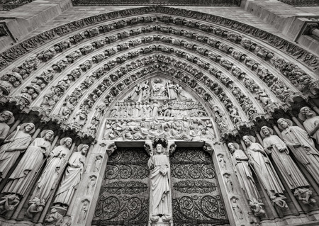 ile de la cite: Central gothic portal of Notre Dame de Paris cathedral featuring bas relief of the Last Judgement. The heavy wooden doors are decorated by intricate iron work. The 13th century cathedral is located in the 4th arrondissement on Ile de La Cite Paris France