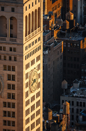 neighboring: Aerial view of early 20th century skyscraper and its clock with neighboring rooftop wooden water tanks at sunset. Madison Square park area Midtown New York City Stock Photo