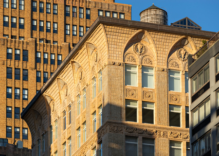 architectural  detail: Sunlit architectural detail of upper floors of a loft building in Chelsea Manhattan New York City. Early 20th century brick architecture with ornamental medallions garlands and rams heads. A grid pattern of terracotta tiles separates gothic arches at the