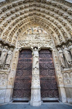 ile de la cite: Notre Dame de Paris cathedral featuring a central gothic portal and bas relief of the Last Judgement. The heavy wooden doors are reinforced by decorative iron work. Ile de La Cite Paris France