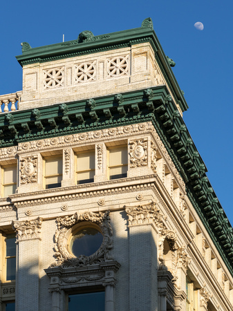 cornice: 1900 century Chelsea building in Beaux-Arts architectural style. The facade is in light colored brick with corinthian capitals and floral ornamentations. The building is capped by a heavy cornice that is painted dark green. Manhattan, New York City Stock Photo