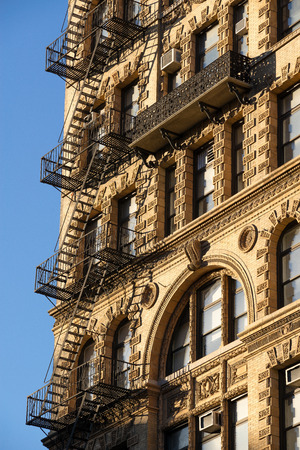 fire escape: Fire escape and ornamented facade with wrought iron balcony on brick building in Chelsea, Manhattan, New York City