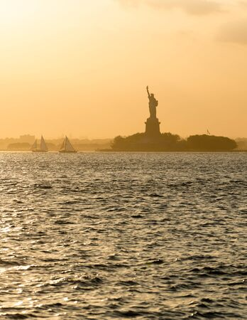 liberty island: Statue of Liberty and Liberty Island across New York Harbor in hazy sunset light. New York City