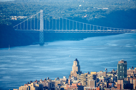 Aerial New York City view of the Hudson River and George Washington Bridge. Late afternoon light illuminates Upper West Side, Manhattan buildings and New Jersey Palisades.