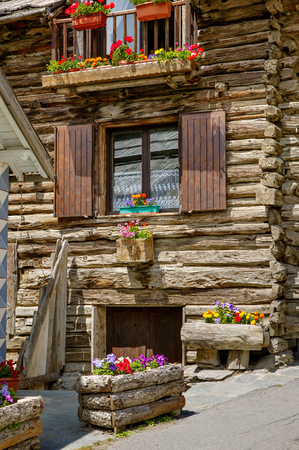 log house: Summer flowers in window boxes decorate a log house in Queyras Nature Park. The roughly constructed wooden house is in the Southern French Alps Hautes-Alpes.