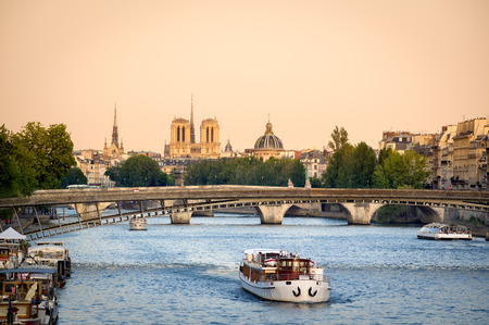 institute is holy: View of the Seine River in Paris with Passerelle de Solferino bridge and passing tour boat. In the distance are Notre Dame Cathedral, the dome of Institut de France and the spire of Sainte Chapelle. Summer evening light. Stock Photo