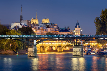ile de la cite: Seine River with reflected evening light. The Pont des Arts and Pont Neuf lead to Ile de la Cite. In the background, the illuminated Notre Dame cathedral rises above the island. Paris, France.