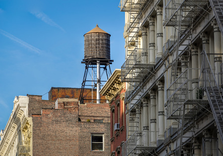 brick walls: Cast iron facades of Soho loft buildings and rooftop wooden water tank, in Downtown Manhattan, New York City Stock Photo
