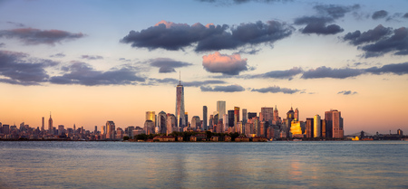 ellis: Lower Manhattan skyscrapers at sunset. Ellis Island appears in front of New York Citys Financial District Stock Photo