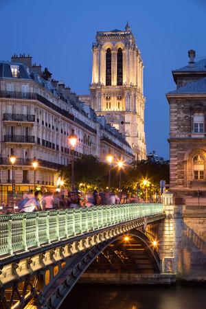 ile de la cite: Pont dArcole leading to Notre Dame Cathedral illuminated in early evening. The bridge crosses the Seine River and joins the Right Bank to Ile de la Cite in Paris, France