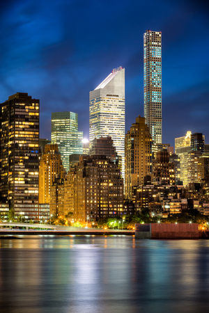 midtown manhattan: Illuminated Midtown Manhattan skyscrapers and city lights are reflected in East River at twilight. New York City Stock Photo