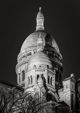 18th: Black  White view of the domes of Sacre Coeur Basilica Sacred Heart in Montmartre. The Romano-Byzantine architectural style basilica is illuminated at night. 18th arrondissement, Paris, France.