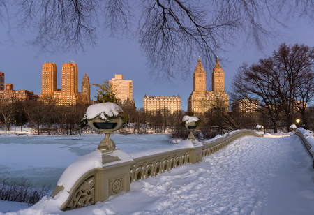 winter sunrise: Central Park Bow Bridge at The Lake and Upper West Side buildings at dawn on a freezing cold winter morning. Winter sunrise in Manhattan, New York City