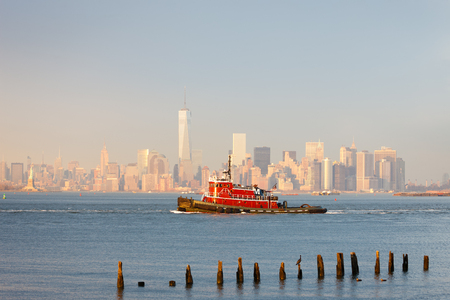 tugboat: Tugboat in New York Harbor in afternoon soft winter light with the Financial District of Lower Manhattan in background.New York City.