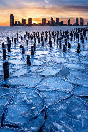 pilings: Winter view of the Frozen Hudson River with old wood pilings at sunset with Jersey City skyscrapers