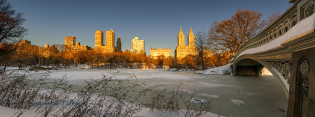 winter sunrise: Panoramic winter sunrise on frozen Central Park Lake with Bow Bridge and view of Upper West Side buildings. Manhattan, New York City Stock Photo
