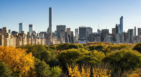 midtown manhattan: Panoramic view from above of Central Park trees with full fall colors. On the right, high-rise buildings of the Upper East Side. In the distance are skyscrapers of Midtown Manhattan, New York City Stock Photo