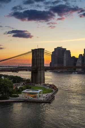 lower east side: Sunset over the Brooklyn Bridge and Carousel with view on the Manhattan Lower East Side Financial District. East River. New York City