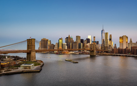 lower east side: Aerial view of the Brooklyn Bridge at sunrise and Manhattan Lower East Side Financial District skyscrapers. New York City