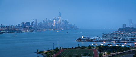 Lower Manhattan with heavy rainfall in evening and Financial District skyscrapers and Weehawken, New Jersey waterfront. New York Stock Photo