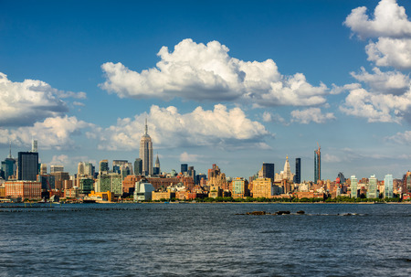 west river: Manhattan Midtown West skyscrapers and Hudson River with passing clouds. Cityscape of a summer afternoon in New York City with view of Midtown and West Village Stock Photo
