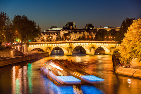 Pont Neuf bridge and Seine River at twilight with city lights and passing tourist boat in summer. Ile de la Cite, 1st and 6th Arrondissement, Paris, France Stock Photo